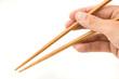 Hand holding chopsticks.