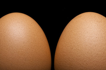 Two brown eggs on black background