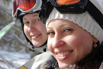 Two smiling female snowboarders on a chairlift.