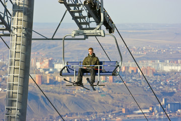 Man on the ski lift above city landscape