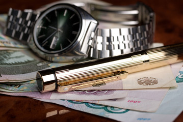 Ink pen, watch and russian roubles