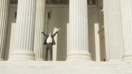 very happy young businessman leaving historical building