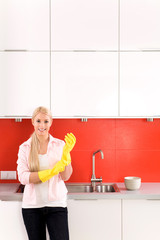 Woman wearing rubber gloves standing in kitchen
