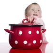 Toddler pretending to cook with a big red pot.