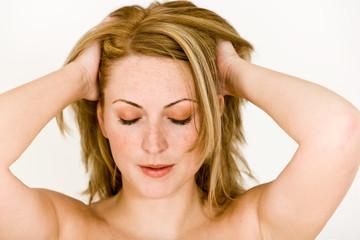 junge Frau mit Hände in Haaren