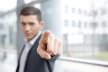 geschäftsmann im anzug zeigt mit finger