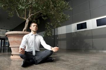 mann sitzt in pause im yogasitz in bürogebäude