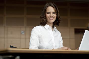 junge frau sitzt vor computer bildschirm und lächelt