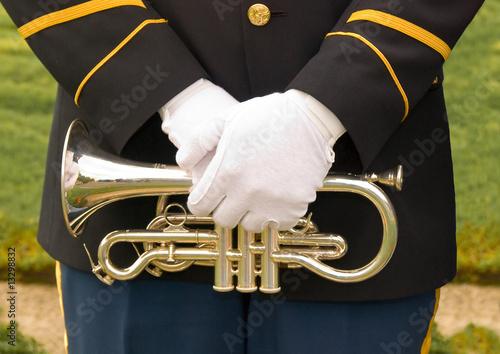 Uniformed military bugler's gloved hands over trumpet. - 13298832