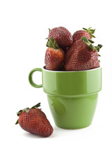 green mug overflowing with strawberries