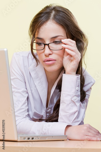 Pretty female secretary with eyeglasses and laptop
