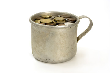 Old aluminum mug and coins  on white background.