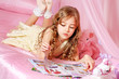 Beautiful little girl reading magazine