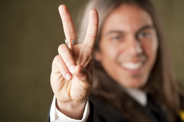 Handsome man in formalwear making a peace sign