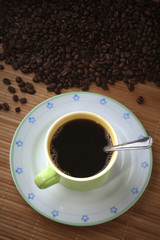 Coffee cup with coffee beans, saucer and spoon