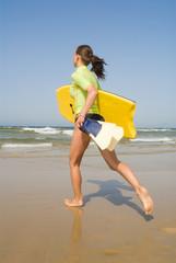Junge Frau mit Boogie Board am Strand