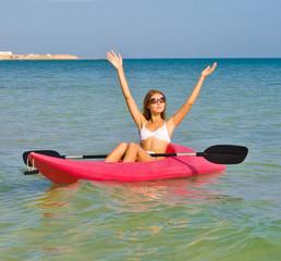 Girl in bikini sailing a kayak