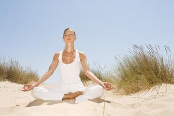 Frau macht Yoga in den Dünen
