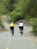Two women on bikes on overcast day trail poster