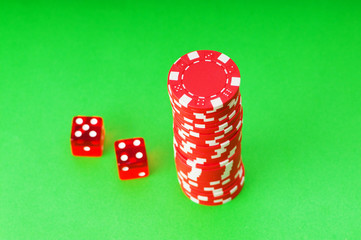 Casino chips and dice against green background