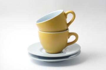 due tazzine gialle per caffè con piattini
