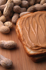 peanut butter sandwich with peanuts on cutting board