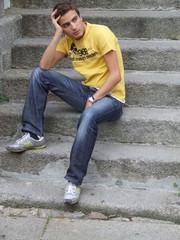 rapaz sentado em escadaria