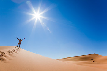 Man standing on a sand dune in the desert; Maroc