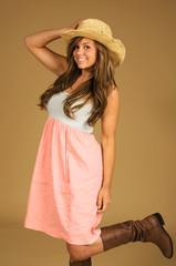 Beautiful brunette in cute summer dress and cowboy hat