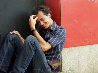 rapaz sentado numa entrada rindo