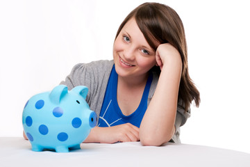 Smiling young girl with blue biggy bank