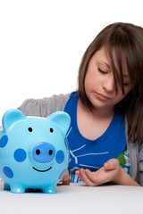 young girl counting money from piggy bank