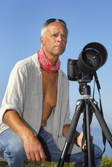 Handsome mature man posing with a big camera