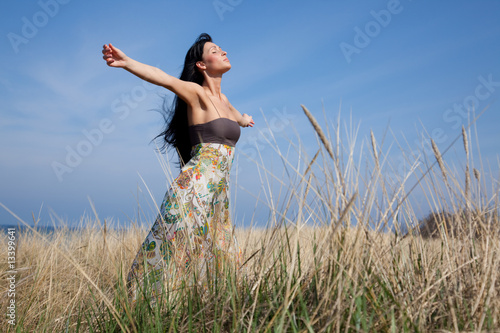 Female feeling free in field on baltic sea