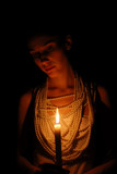 Girl with burning candle in darkness