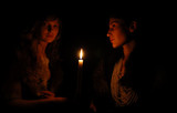 Women on each side of candle in the dark