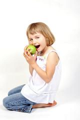 Kniendes Mädchen beisst in Apfel