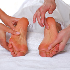 Four hands do massage to two female feet