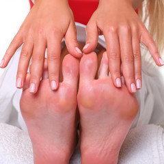 Young woman shows the well-groomed heels and manicure on hands