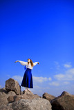 Girl model in a blue dress against a background of blue sky