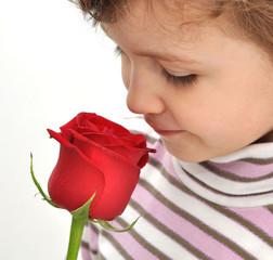 bambina che annusa una rosa