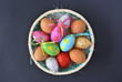 Basket with fresh and Easter eggs isolated on black