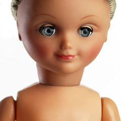 detail of face of plastic doll  isolated on white