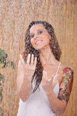 young woman in white shirt under shower