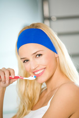 Young happy woman clean teeth by tooth-brush in bathroom