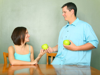 Male Caucasian Giving Green Apple To Young Woman