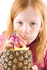 red head girl is drinking from a fresh pineapple on white