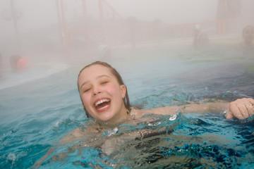 Sophie schwimmt im  beheizten Kurbades im Dunst im Winter