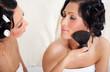2 women brush  skin powder
