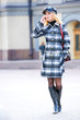 Beautiful young blond in a coat talks on the phone